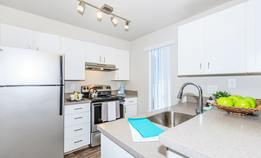 Image of kitchen featuring stainless steel refrigerator, stove and upgraded lighting with white cabinets.