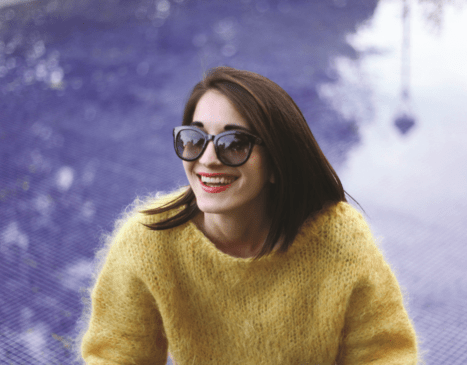 Woman in sunglasses and sweater smiling