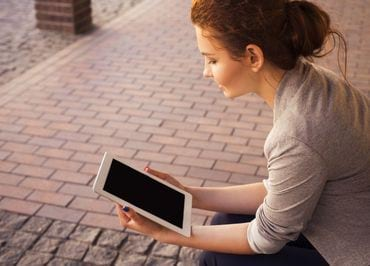 Brunette woman looking at iPad while sitting outside on a stoop