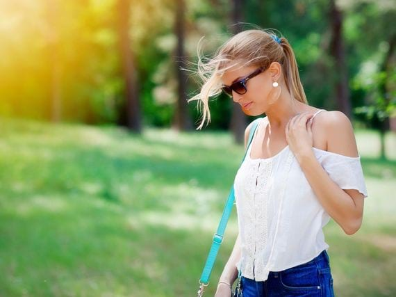 Blonde woman with sunglasses strolling through park