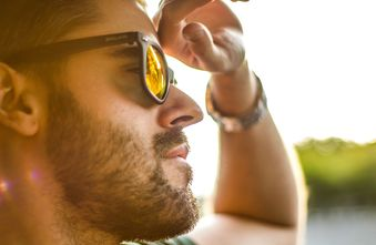 Brunette Man with sunglasses gazing forward with sunlight on his face
