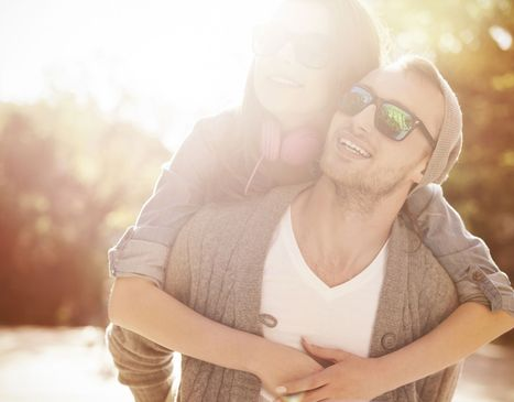 Couple in sunglasses smiling together outdoors in the sunshine