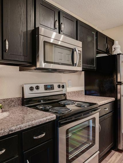 Furnished model kitchen area with stainless appliances and granite style counters