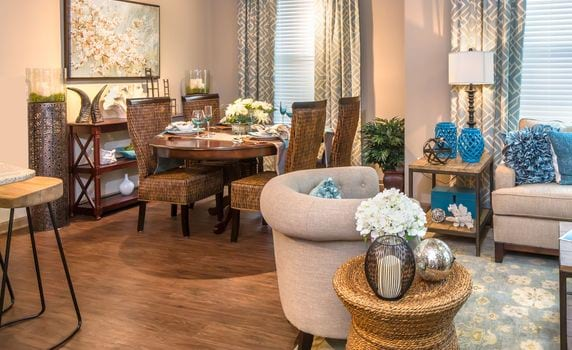Furnished model dining room area with seating and decor