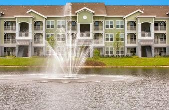 View of pond and fountain with apartment building exteriors in the back