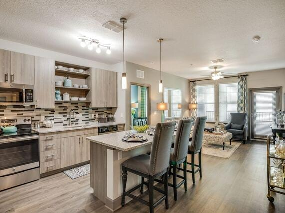 View of furnished model kitchen with stainless appliances and granite countertops