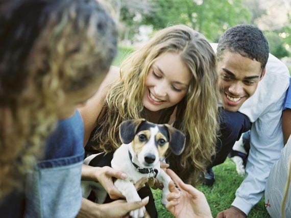 Group of friends smiling with puppy outside