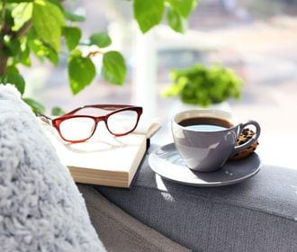 FAIRBANKS SQUARE - stock image of a coffee cup, book and glasses resting on the arm of a chair