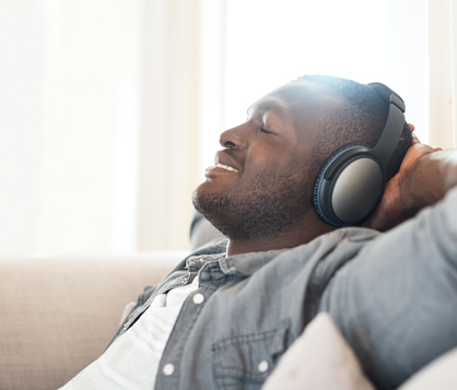 Man with headphones on lounging with hands behind head and eyes closed