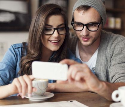 Man and woman in cafe looking at phone together and smiling