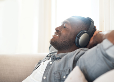 Male with headphones on lounging on couch with hands behind his head while looking up andsmiling