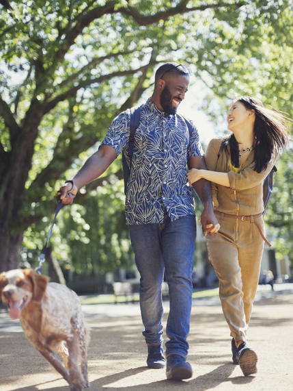 Man and woman walking through park with dog on leash while smiling and laughing at each other.