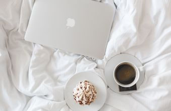 View from above of laptop, muffin and coffee on white bedspread.