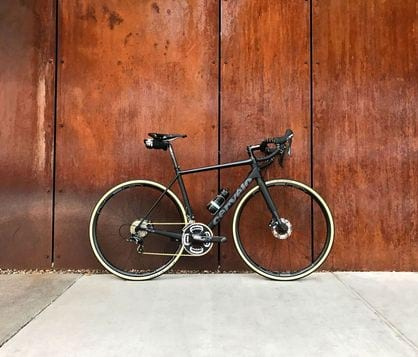Stock image of bike against wood panel wall.