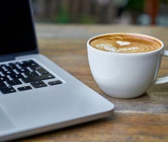 FAIRBANKS TERRACE - stock photo of a laptop and a coffee cup on top of a table