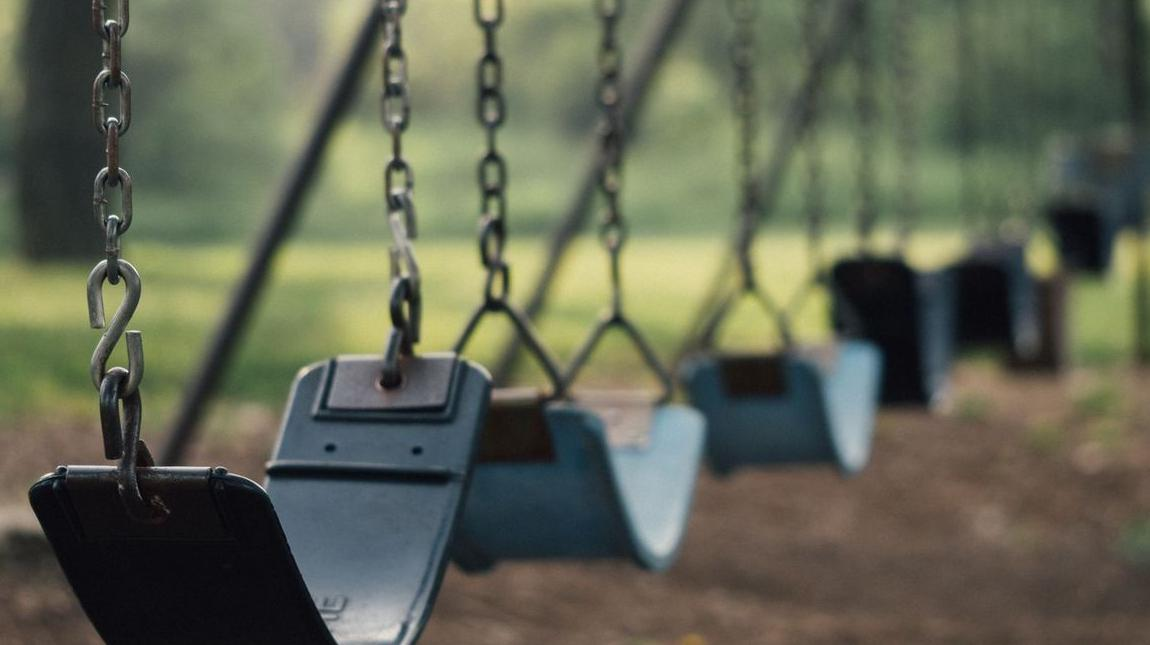 IRIS APARTMENTS - stock photo of swings on a playground