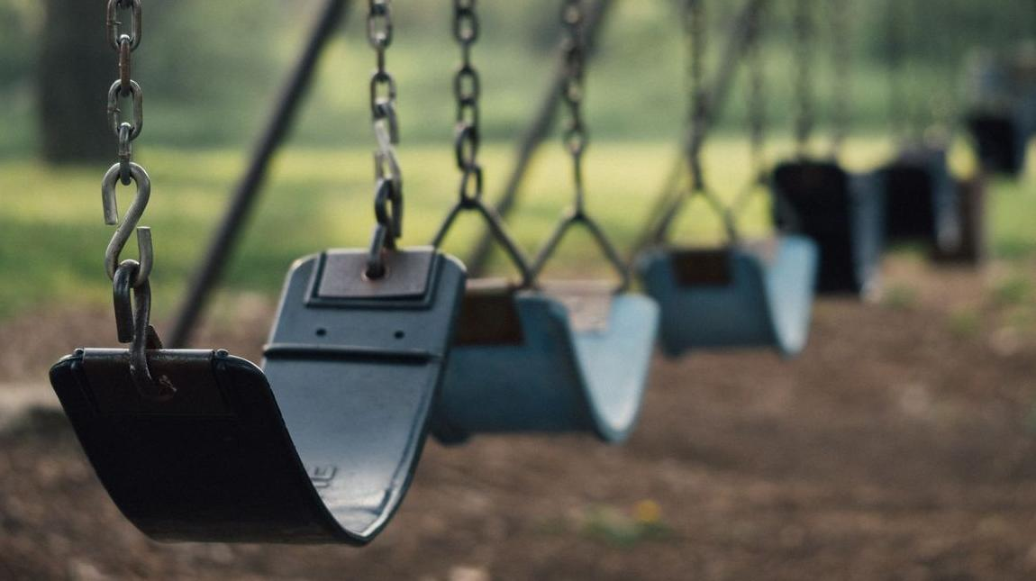 The Crossings Apartments - stock photo of swings at a playground