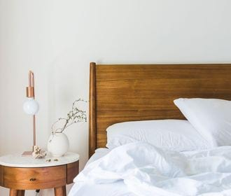 Westminster Manor - stock photo of a headboard and bed with a nightstand, flower vase, and lamp on top