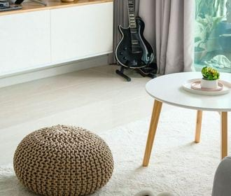 Stock photo of a living Room area with guitar and tv in the distance with a coffee table and slippers on rug