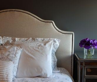 Villa Serena - stock photo of a headboard and bed with pillows, a nightstand with small glass vase with flowers on top