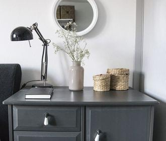 Westminster Manor - stock photo of a cabinet table that has a plant, book, lamp and 2 small baskets on top with a mirror hanging on the wall