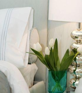Seabreeze Farms - stock photo of a headboard and bed with a nightstand, flower vase, and lamp on top