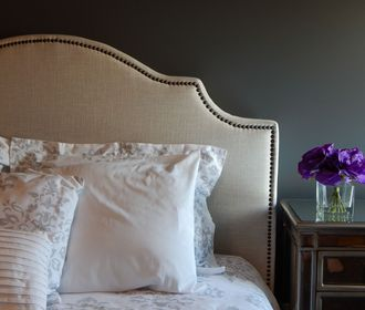 Villa Lara - stock photo of a headboard and bed with pillows, a nightstand with small glass vase with flowers on top