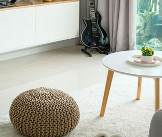 stock photo of living room with a guitar on a stand, coffee table and ottoman