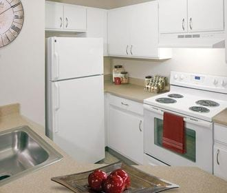 Image of kitchen with refrigerator, electric stove, tan counters, and white cabinets.