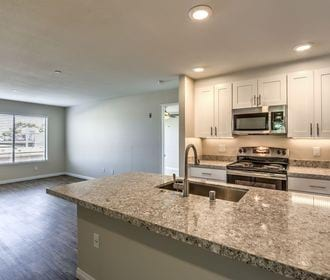 Vinyl floored kitchen with granite counters, stainless steel appliances, and white shaker cabinets.