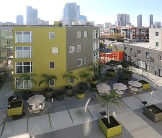 Resident courtyard with picnic tables, planters, and aerial view of San Diego.