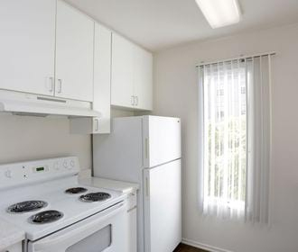 Kitchen with white appliances, white cabinets, and thin window.