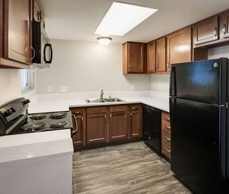 Camden Park - Kitchen with oak cabinets Formica counters, wood-style plank flooring, and black appliances.