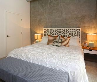 Spacious bedroom with model furniture including a bed and two end tables.