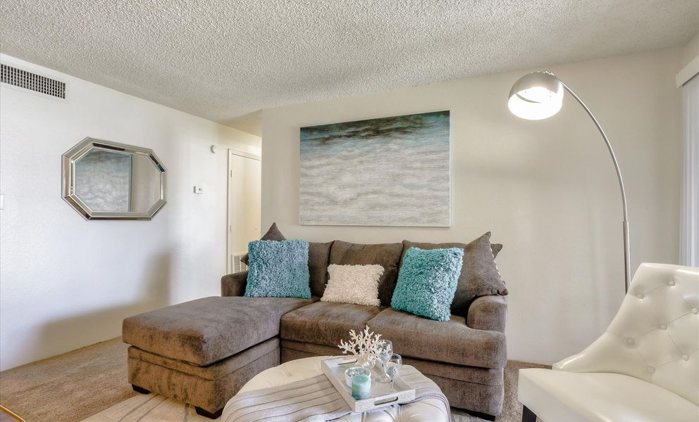 Image of spacious living room with plush carpeting and access to the patio.