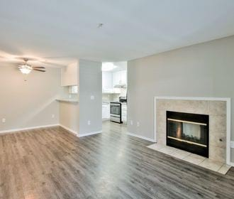 Image of an upgraded apartment with new wood-style flooring, fire place, ceiling fan and new kitchen cabinets.