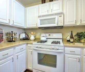 Kitchen with white cabinets and white appliances.