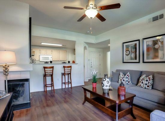 Image of model apartment interior with bar stool seating, fire place, sofa, and wood vinyl flooring.