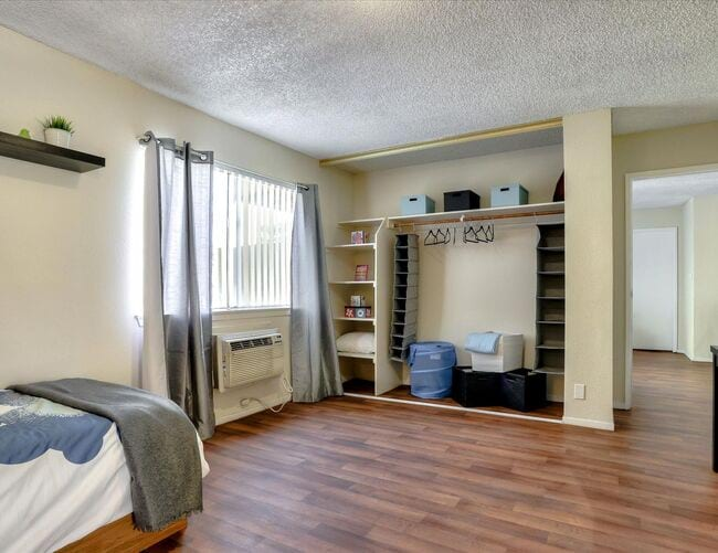 Image of bedroom with spacious closet, bed, white walls, and wood vinyl flooring.
