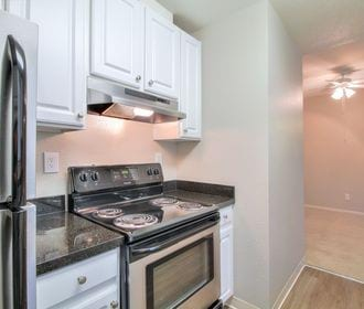 Image of apartment kitchen with white cabinets, granite counters and wood-style flooring.