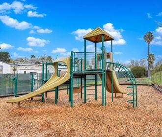 Community playground with slide, climbing bars, and blue sky in background.