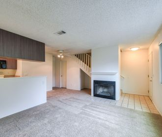 Carpeted living room with ceiling fan, fireplace, tiled entry, and under-staircase storage.