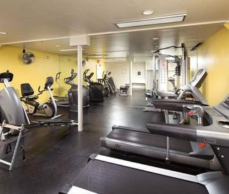 Fitness center with weight machines, cardio machines, and fan.