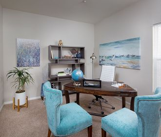 Second bedroom or office with desk and light blue seats.