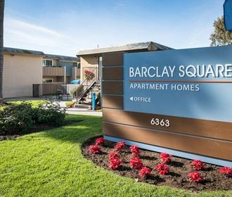 Barclay Square monument sign with wood border, floral landscaping, and view of building exterior.