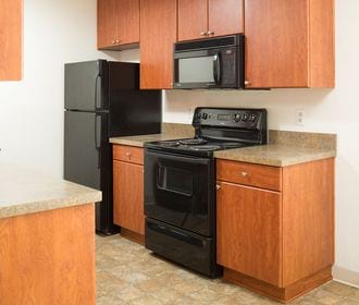 Tiled kitchen with black appliances, laminate counters, and maple slab cabinets.
