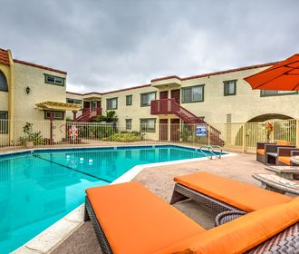 Pool area with orange lounge seating, picnic table with umbrella, and view of tan community exterior