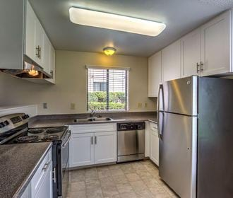 Tiled kitchen with stainless steel appliances, white shaker cabinets, and window.