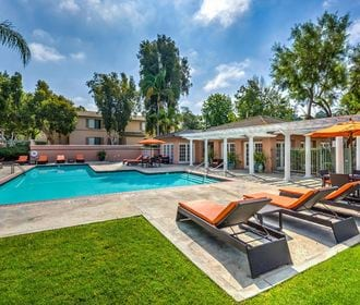 Pool area with orange lounge chairs, picnic table, white pergola, and green lawn.