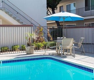 Pool area with picnic table, blue umbrella, fence, and bushes.